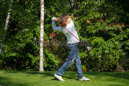 young golf player with driver teeing