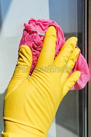 hand in yellow glove washing window