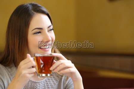 happy woman thinking holding a cup