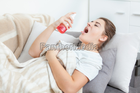 woman using throat spray while lying