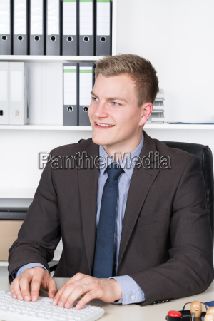 young businessman taps on keyboard