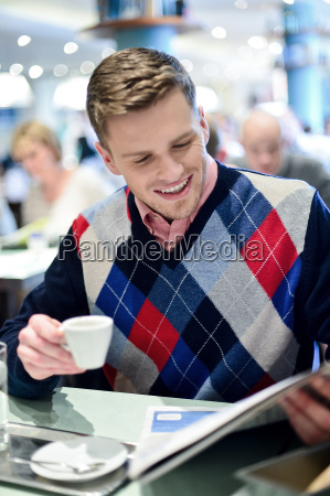 guy reading newspapers and drinking coffee