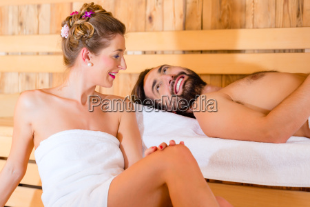 couple sitting in wellness spa sauna