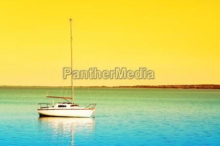sailboat in sunrise at lake balaton