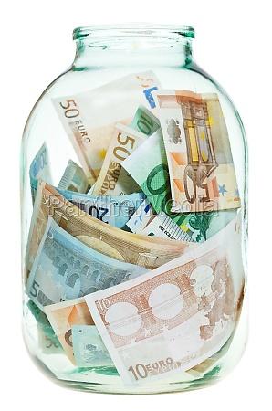 saving euro money in glass jar