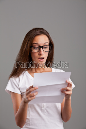 girl reading astonishing news on white