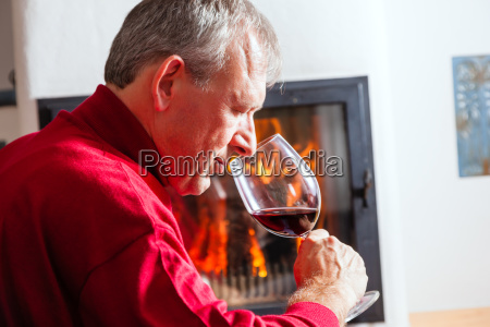 man drinking red wine on fireplace