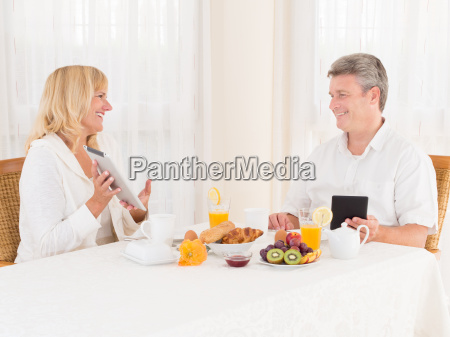 happy mature healthy couple using tablets