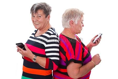 two senior communicate via mobile phone