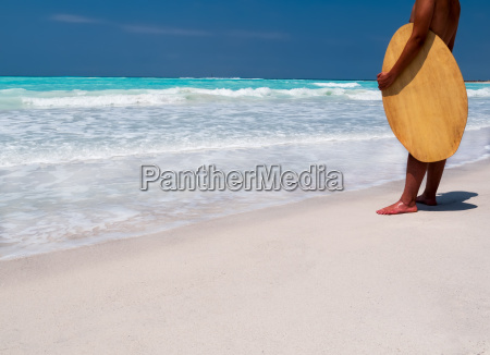 surfer standing on a tropical beach