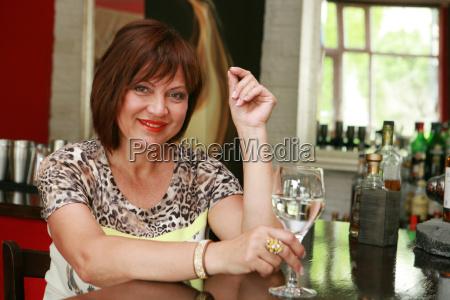 woman sits at a bar counter