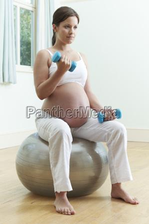 schwangere frau sitzt auf uebungs ball