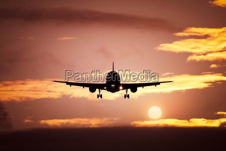plane in the sunset sky