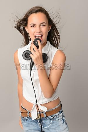 beautiful teenage girl singing with microphone