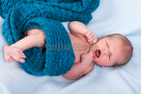 newborn baby wrapped scarf into a