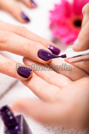 woman gets her nails painted purple