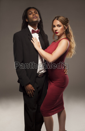 cute young mixed couple against black