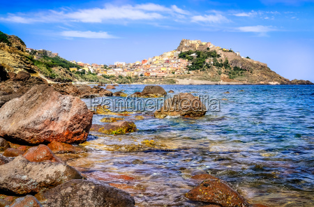 rocky ocean coastline with colorful town