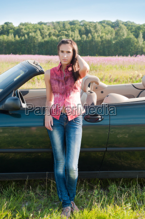 young woman standing near car