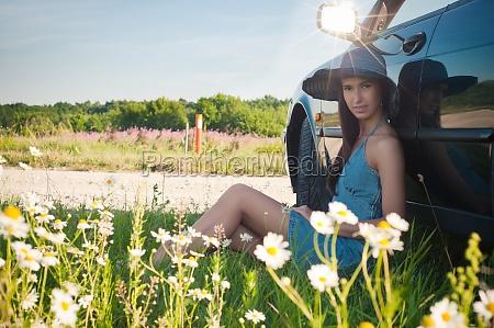 young pretty woman sitting near green