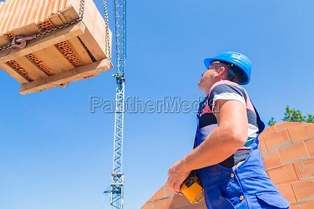 crane operator delivers pallet bricks on