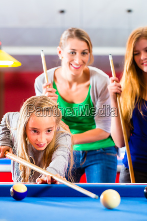 girl playing pool with family