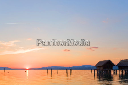 sunset on lake constance with boathouses