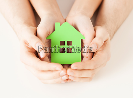 couple hands holding green house