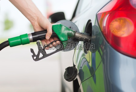 man pumping gasoline fuel in car