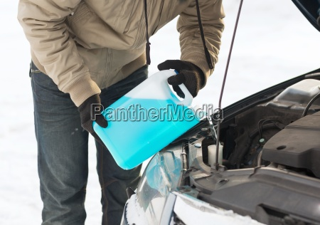 closeup of man pouring antifreeze into
