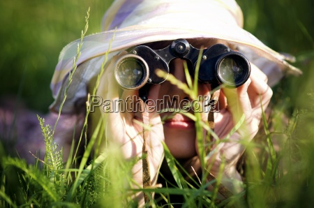 young woman looking through binoculars in