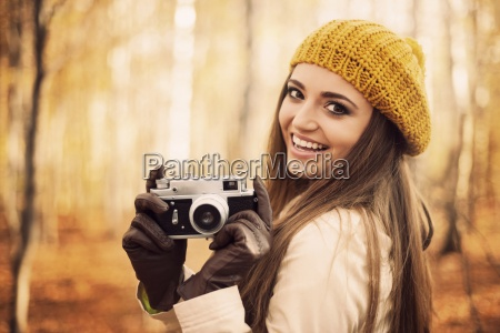 smiling young woman holding retro camera
