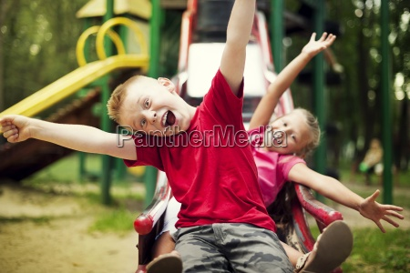 two kids slide on playground
