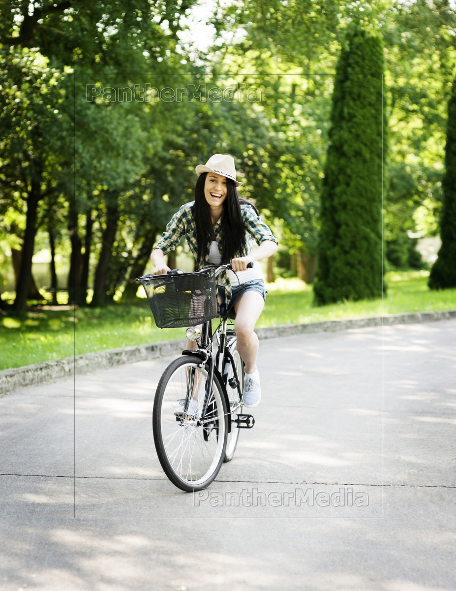 happy, young, woman, riding, a, bicycle - 12117810