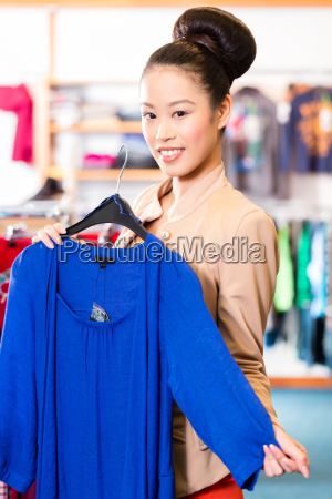 woman chooses clothes in shop while