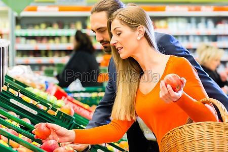 casal pega frutas no mercado de