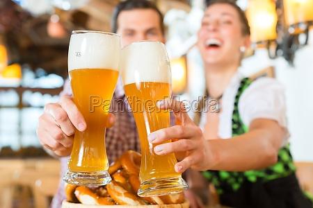 bavarian couple clinking beer