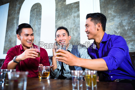 asian friends drinking shots in nightclub