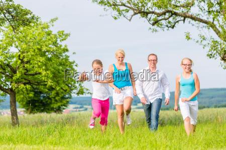 family runs across field or meadow