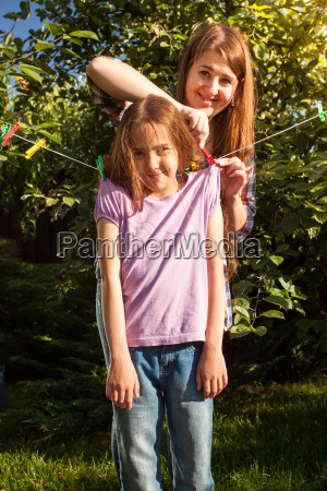 woman hanging girl on clothesline at