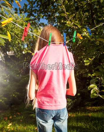 little girl hanged by clothespins on