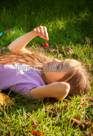 little girl lying on grass and