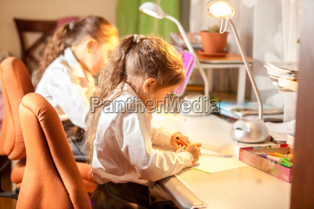 little girls drawing pictures behind desk