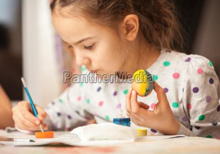 little girl painting egg on christian