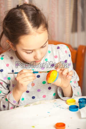 little girl painting easter egg with