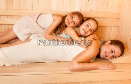 little, girls, lying, on, mothers, back - 12221202