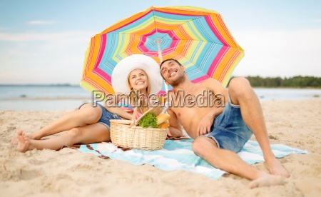 smiling couple sunbathing on the beach