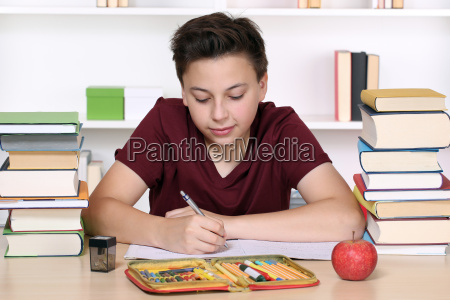 young boy writing homework at school