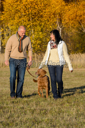couple walking dog in autumn sunny