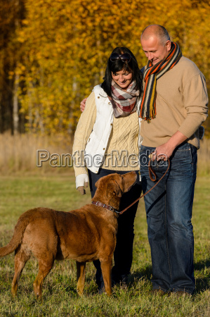 couple with dog in sunny autumn